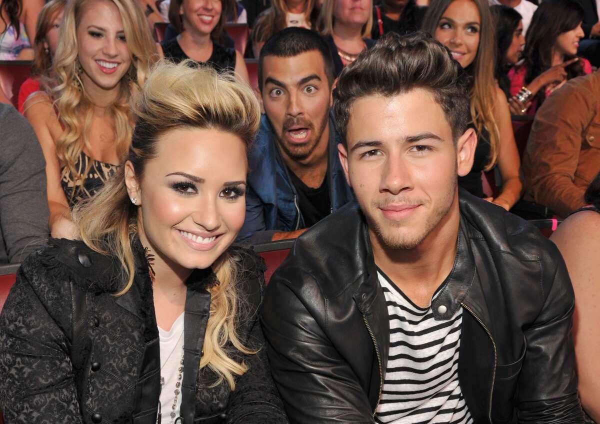 Musicians Demi Lovato, Joe Jonas, and Nick Jonas attend the 2013 Teen Choice Awards at Gibson Amphitheatre on August 11, 2013 in Universal City, California.