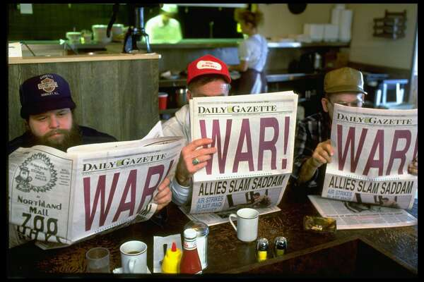 3 men reading local DAILY GAZETTE newspaper w. headline: WAR!, at Friendship House restaurant, on morning after Operation Desert Storm began. (Photo by Steve Liss/The LIFE Images Collection/Getty Images)