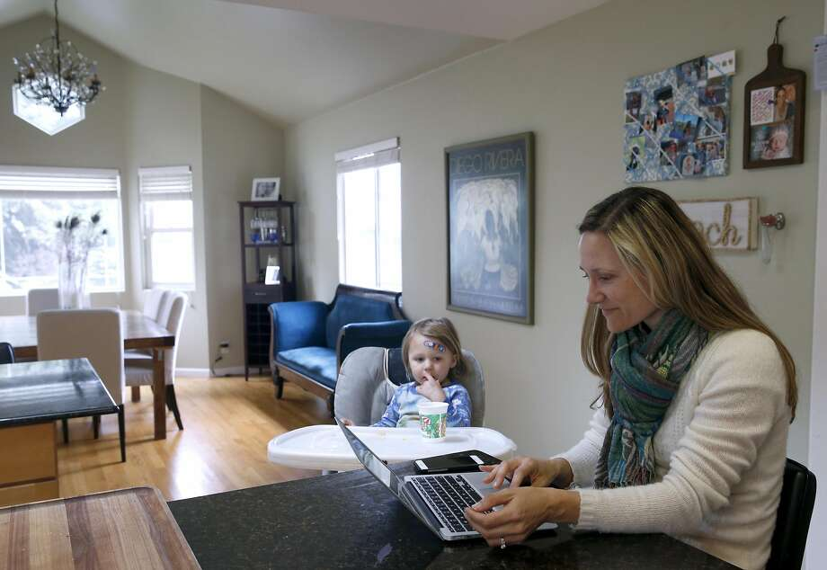Caitlin King checks email while her two-year-old son snacks at their home in Pacifica. Photo: Paul Chinn, The Chronicle