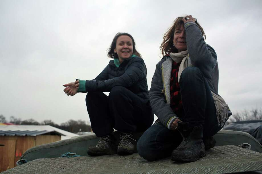 In this Feb. 4, 2016 photo, volunteer Liz Clegg, right, poses with her daughter Inca Sorrell, in the migrant camp of Calais, north of France. The text message from a young boy, writing in broken English on a no-frills cellphone, was frightening enough to set off a frantic, trans-Atlantic search that saved the lives of 15 migrants trapped in a locked truck in England. The message flashed on the cellphone of volunteer Liz Clegg, who in March had handed out hundreds of basic cellphones to children living in the squalid migrant camp in Calais, France, and told them to text in any crisis. (AP Photo/Thibault Camus) Photo: Thibault Camus, STR / AP
