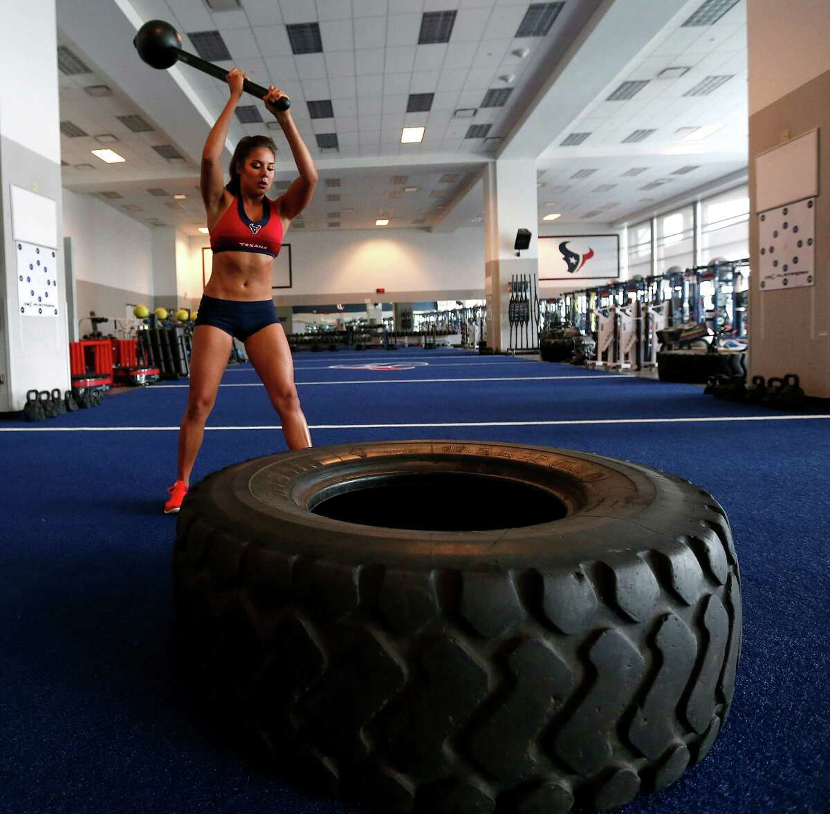 Madison works her upper body and core by hitting a truck tire with a sledge hammer while working out at the Texans weight room.