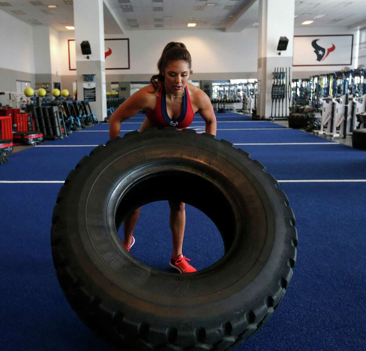 Madison, a Houston Texans cheerleader works out by flipping a giant truck tire in the Houston Texans weight room, Wednesday, April 6, 2016, in Houston. ( Karen Warren / Houston Chronicle )