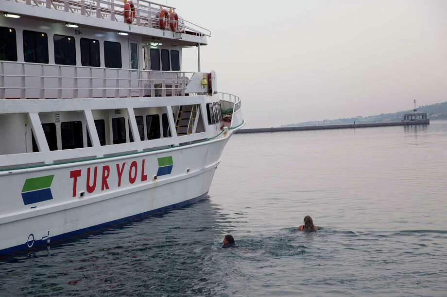 Activists swim Friday as they try to interfere the deportation of Pakistani migrants on board a ferry set to sail for Turkey in the port of Mytilini of the Greek island of Lesbos. Forty-five migrants from Pakistan were deported to Turkey on Friday under the EU agreement with Turkey.  Photo: Petros Giannakouris, STF / AP