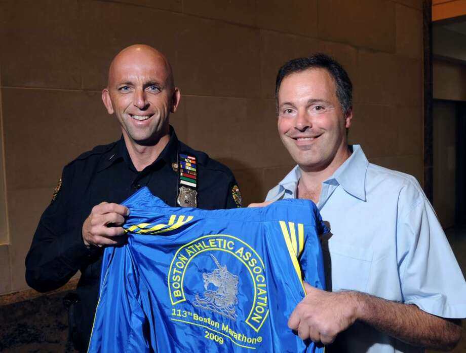 Greenwich Police Officer William Larkin, left, posed with fellow officer, Sgt. Roger Petrone, at Greenwich Police Department headquarters,  April 9, 2010.  Larkin and Petrone are holding the jacket that Larkin received for participating in last year's Boston Marathon.  This year Larkin is running the Boston Marathon again in support of Petrone who is fighting Lou Gehrig's disease. Photo: Bob Luckey / Greenwich Time