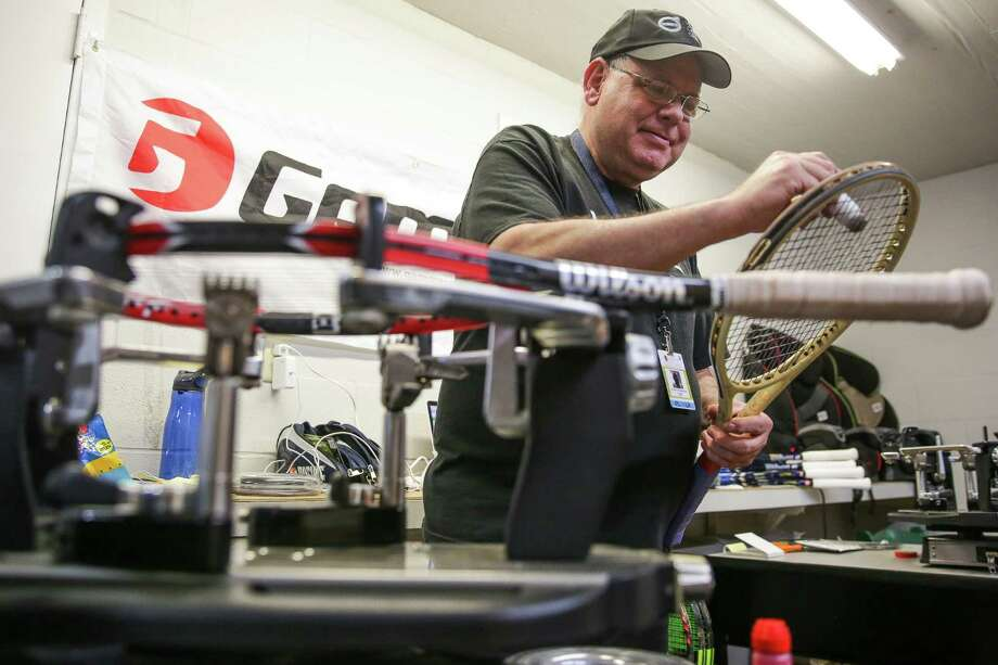 Tennis-racket stringer Chuck Hakansson paints a logo on a restrung racket in a room outside the U.S. Men's Clay Court Championship at the River Oaks Country Club. Photo: Michael Ciaglo, Staff / © 2016  Houston Chronicle