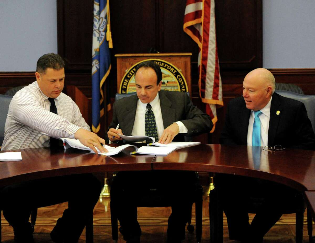 Bridgeport Mayor Joe Ganim, flanked by Sgt. Chuck Paris and Police Cheif Armando Perez, formally signed off on a four-year police contract that expires June 30. The contract, three-years in the making and approved a year ago, was signed during a ceremony at the Margaret Morton Government Center in Bridgeport, Conn. on Friday, April 8, 2016.