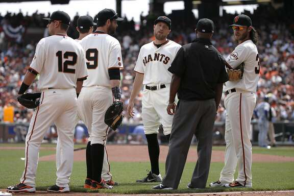Giants' ) l to r) Joe Panik, Brandon Belt, Hunter Pence and Brandon Crawford wait for the decision in a play-under-review in the second inning that went to the Dodgers, as the San Francisco Giants take on the Los Angeles Dodgers during their home opener of the 2016 MLB season, at AT&T Park in San Francisco, California on Thurs. April 7, 2016.