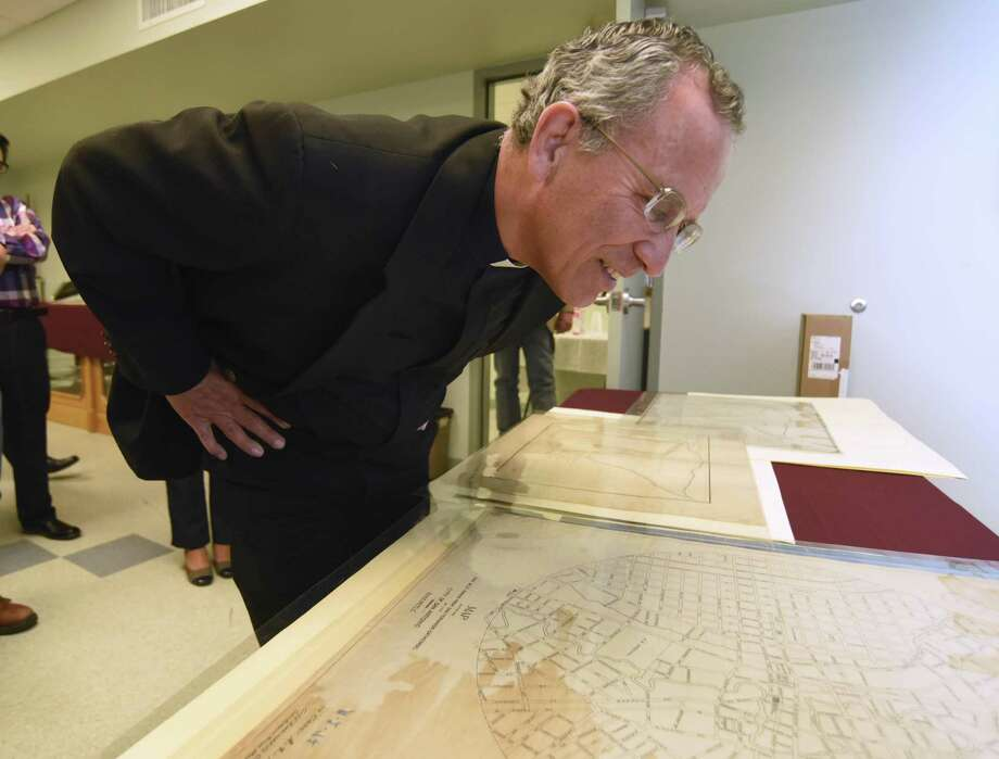 Father David Garcia examines a circular map of the city of  San Antonio dating back to 1911 during the Tricentennial Commission's History and Education Subcommittee tour of the Municipal Archives and Records Facility on Friday, April 8, 2016. Photo: Billy Calzada, Staff / San Antonio Express-News / San Antonio Express-News