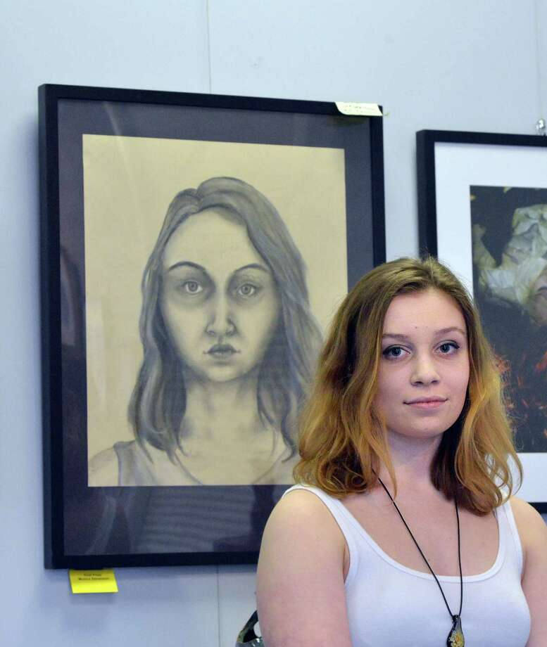 Greenwich High School senior Monica Stevenson,18, with her self-portrait done in charcoal that was part of the Art Society of Old Greenwich Spring Art Show at the Garden Education Center in Cos Cob, Friday night, April 8, 2016. Stevenson was one of three GHS student scholarship award winners along with Estella Perrone for surrealistic photography and Andreas Zervos for ceramics. Barbara Stretton of the Art Society of Old Greenwich said there are about 35 works in the show and that the show will be available for viewing at the center until April 29th. According to Stretton viewing hours are during the week, Monday to Friday, 9 am to 4 pm. Photo: Bob Luckey Jr. / Hearst Connecticut Media / Greenwich Time