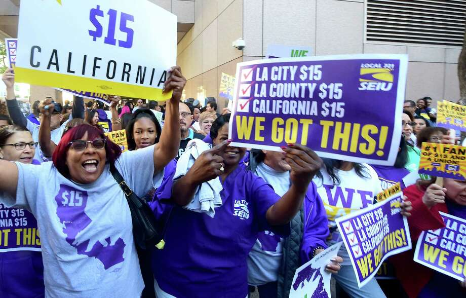 Workers celebrate outside the Ronald Reagan State Building in downtown Los Angeles, where Gov. Jerry Brown signed the bill that will raise the state's minimum wage to $15 an hour by 2022. Photo: FREDERIC J. BROWN, Stringer / AFP or licensors