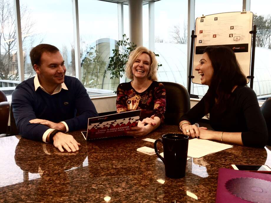 Kariann Morris, center, and her research analyst Natalie Pollard, right, meet with client Wesley Horth of Bay State Elevator