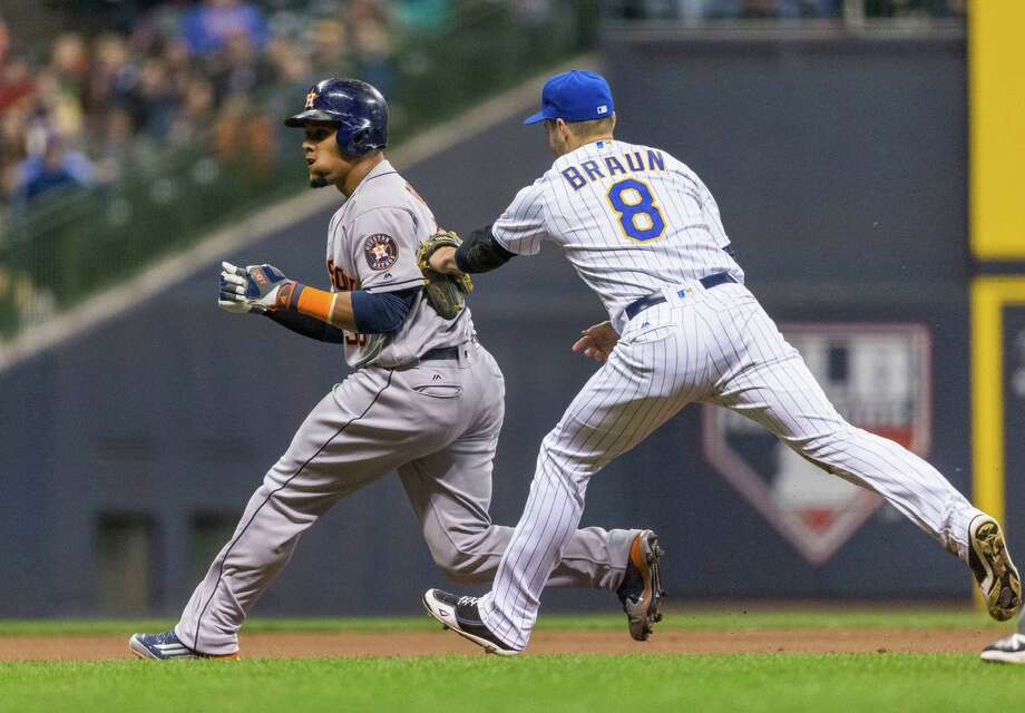 The Astros' Carlos Gomez, left, is caught trying to steal third and instead forces a rundown until being tagged out by the Brewers' Ryan Braun during fourth-inning action Friday night. Photo: Tom Lynn, FRE / FR170717 AP