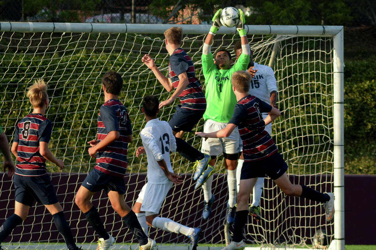 Elsik junior goalkeeper Pablo Torres, center, makes a save in front of Tompkins junior forward Alex Bruce during the second half of their 2016 Region III-6A Soccer Championships semifinal matchup at Abshier Stadium in Deer Park on Friday, April 8, 2016. (Photo by Jerry Baker/Freelance)