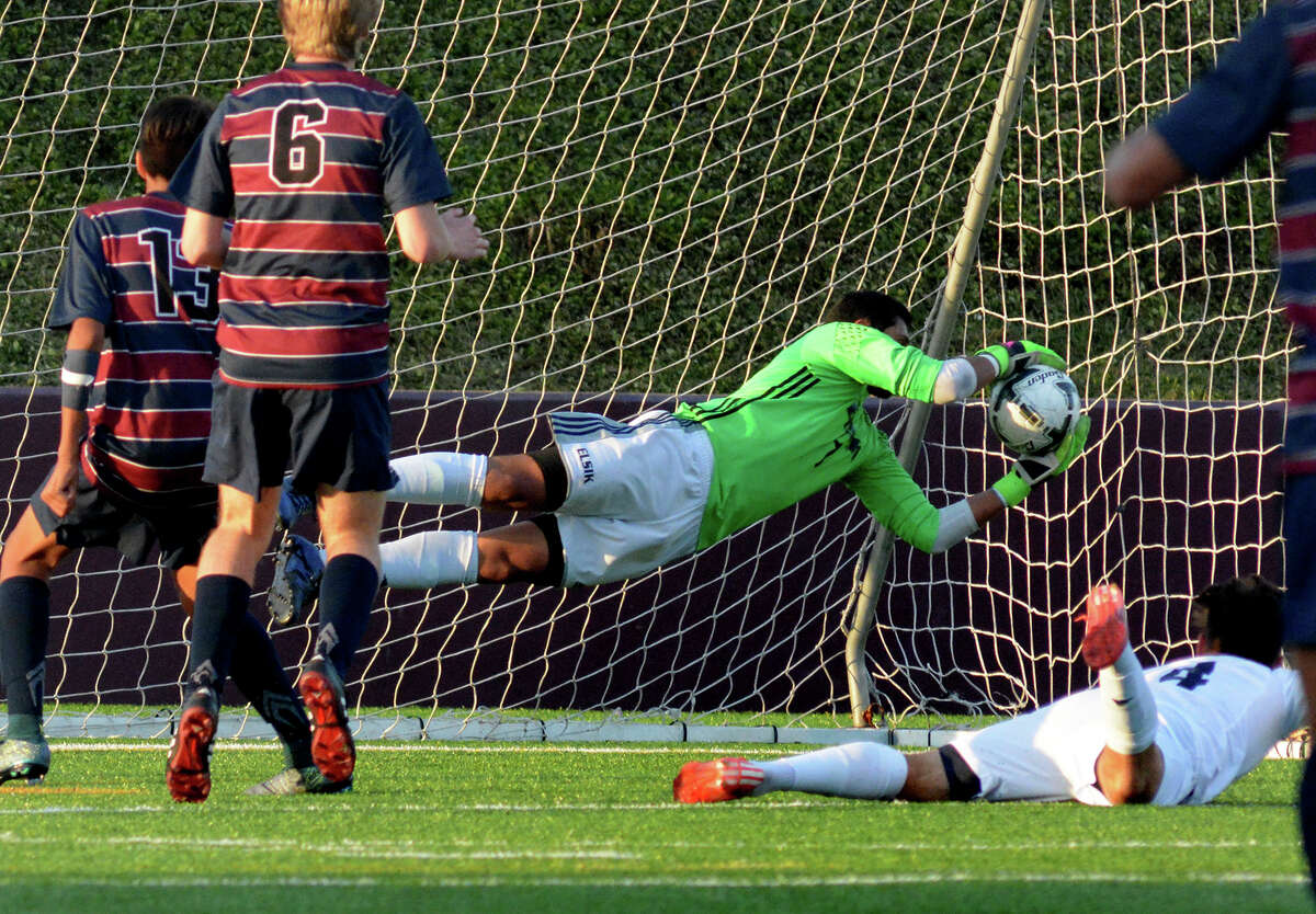 Elsik junior goalkeeper Pablo Torres, center, goes vertical to make a save in front of Tompkins freshman midfielder Jovan Prado (13) and junior forward Alex Bruce (6) during the second half of their 2016 Region III-6A Soccer Championships semifinal matchup at Abshier Stadium in Deer Park on Friday, April 8, 2016. (Photo by Jerry Baker/Freelance)