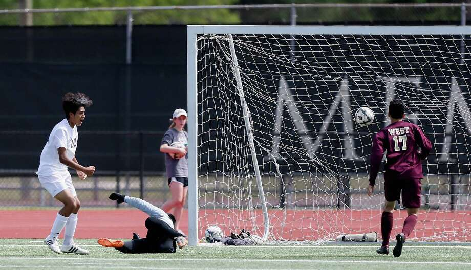 Mitchell Medrano, left, scores on Magnolia West goalkeeper Michael Ruiz to give Goose Creek Memorial the victory and spot in the regional final. Photo: Bob Levey, For The Chronicle / ©2016 Bob Levey