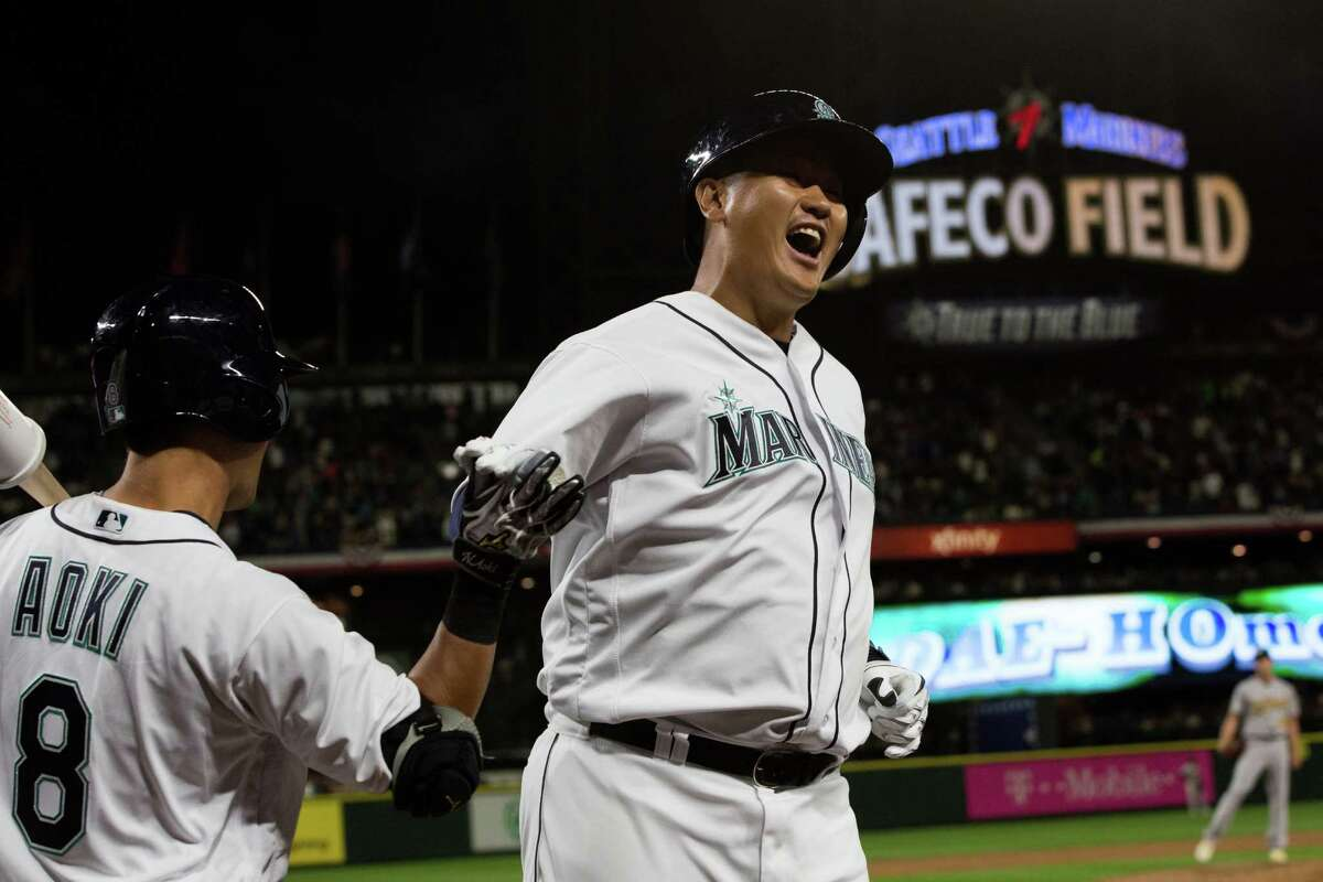 Mariners first baseman Dae-Ho Lee gets a high five from Nori Aoki after scoring a home run in the fifth inning in a baseball game against the Oakland Athletics at Safeco Field on Friday, April 8, 2016.