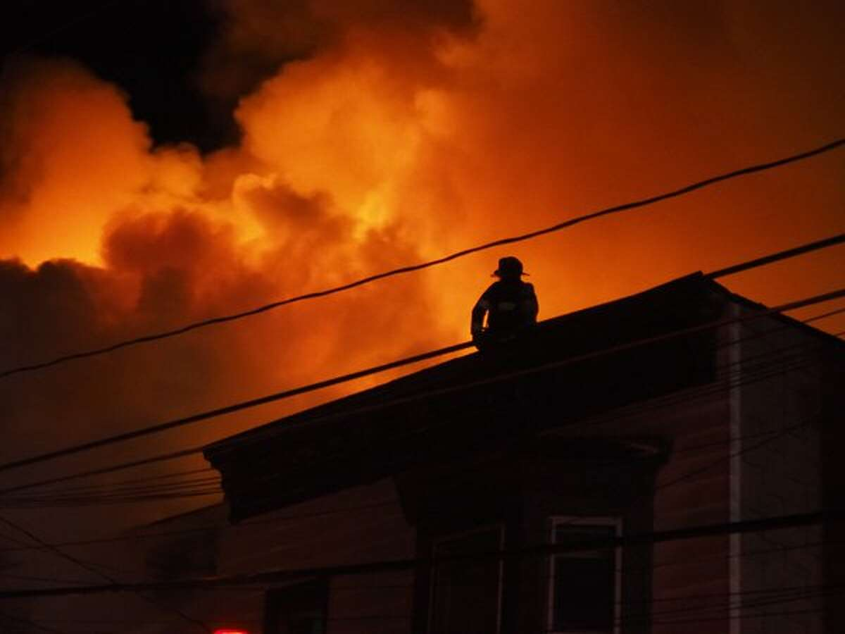 A firefighter attacks a blaze in Cohoes where at least three houses are affected. (J.p. Lawrence / Times Union)