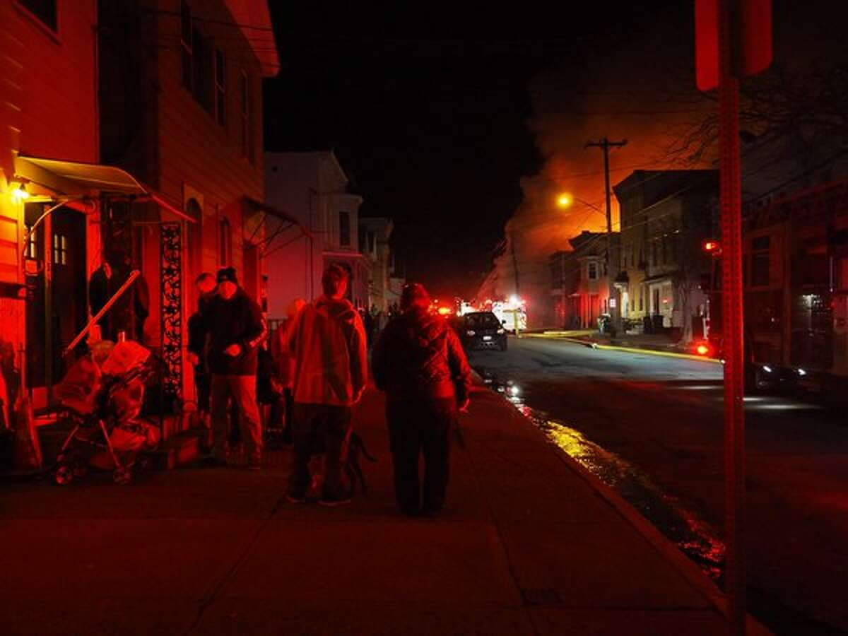 Fire casts a glow on Cohoes residents as firefighters battle a nearby blaze Friday April 8, 2016 (J.p. Lawrence / Times Union)