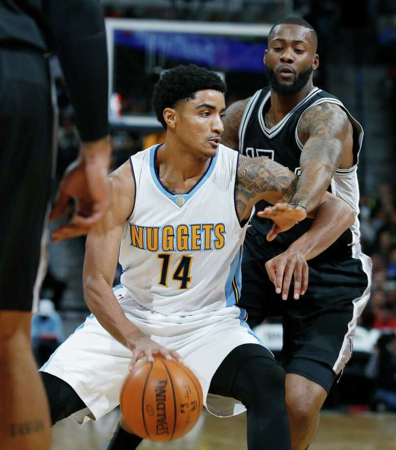 Denver Nuggets guard Gary Harris, left, drives the lane for a basket as San Antonio Spurs guard Jonathon Simmons defends in the first half of an NBA basketball game Friday, April 8, 2016, in Denver. (AP Photo/David Zalubowski) Photo: David Zalubowski, STF / AP / Copyright 2016 The Associated Press. All rights reserved. This material may not be published, broadcast, rewritten or redistribu