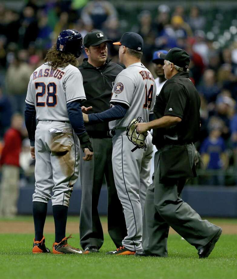 Astros manager A.J. Hinch and Colby Rasmus, left, argue a call by umpire Mike DiMuro, center, that ended Friday's game. Rasmus was called out for an improper slide into second base on a double-play grounder. Photo: Dylan Buell, Stringer / 2016 Getty Images