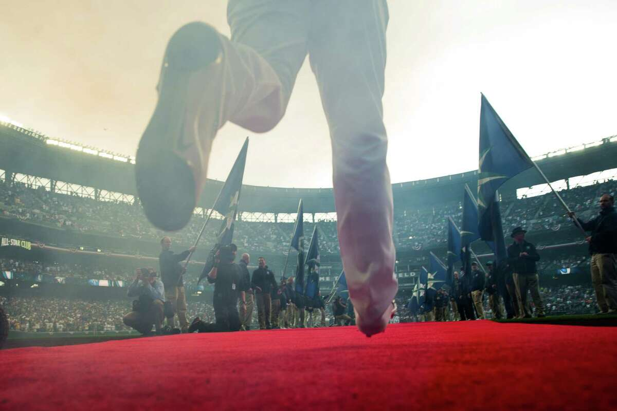 Mariners outfielder Franklin Gutierrez runs down the red carpet as he's announced at the teams' 2016 home opener against the Oakland Athletics at Safeco Field on Friday, April 8, 2016.