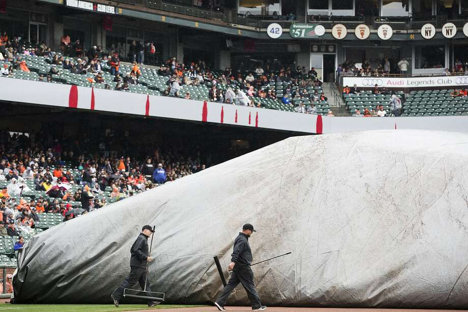 Members of the Giants grounds crew remove the tarp covering the field during a rain delay before the Giants take on the Los Angeles Dodgers at AT&T Park in San Francisco, Calif. on Saturday, April 9, 2016. Photo: Stephen Lam, Special To The Chronicle