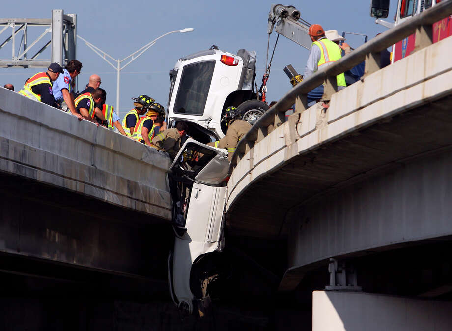 Emergency crews work to free a driver from an SUV that became wedged between the Interstates 35 and 37 interchange on May 11, 2007. The driver, who wasn't seriously hurt, was being chased. Photo: Edward A. Ornelas /San Antonio Express-News / SAN ANTONIO EXPRESS-NEWS