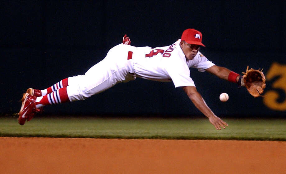 Memphis Redbirds shortstop Wilson Delgado dives for a ball hit by St. Louis Cardinals' Jim Edmonds during an exhibition game in Memphis, Tenn., Friday, April 2, 2004. Delgado trapped the ball, and Edmonds was safe at first. (AP Photo/The Commercial Appeal, Nikki Boertman) Photo: NIKKI BOERTMAN, MBR / AP / THE COMMERCIAL APPEAL