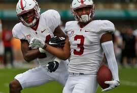 Quenton Meeks, left, and Noor Davis celebrate a successful defensive play during Stanford's Cardinal and White spring football game in Cagan Stadium April 9, 2016 in Palo Alto, Calif.