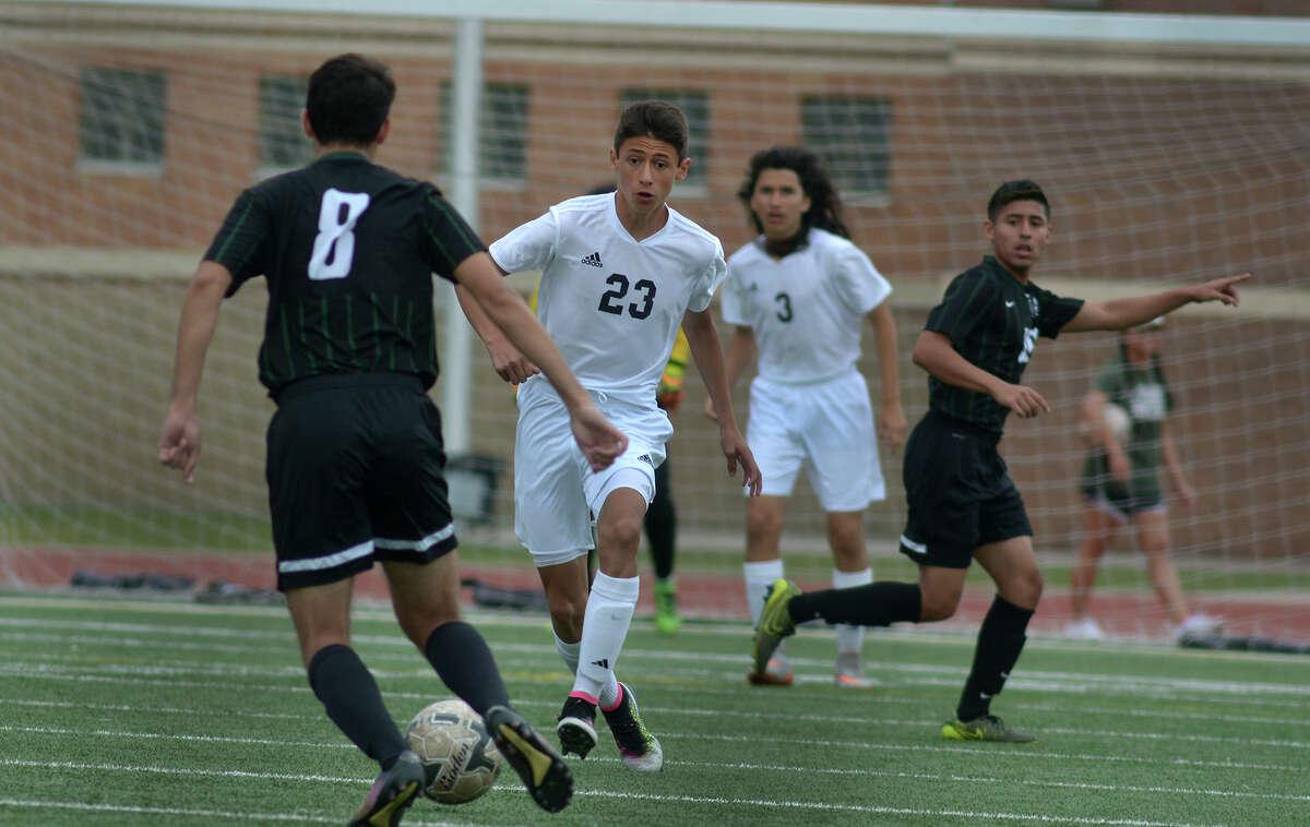 Goose Creek freshman striker Brian Diaz (23) tries to work the ball past Pflugerville Connally senior midfielder Daniel