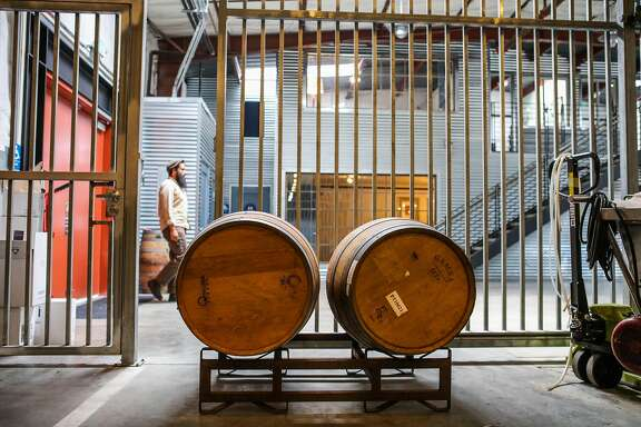 Eli Silins (left), the cellar master walks down the hall of kosher winery, Covenant Wines in Berkeley, California, on Wednesday, April 6, 2016. One of the ways it is kept kosher is by having a metal gate to separate the offices from the cellar.
