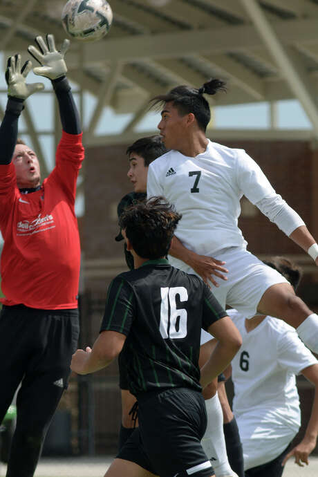 Goose Creek Memorial's Miguel Sanchez (7) tries to get a header past Pflugerville Connally goalkeeper Ty Hurley in the first half. Photo: Jerry Baker, Freelance