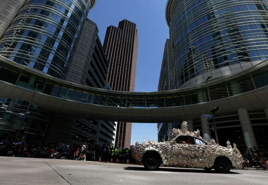 The Art Car Museum's shell car swims through the downtown crowds Saturday at the 29th annual Houston Art Car Parade.  Photo: Elizabeth Conley, Staff / © 2016 Houston Chronicle