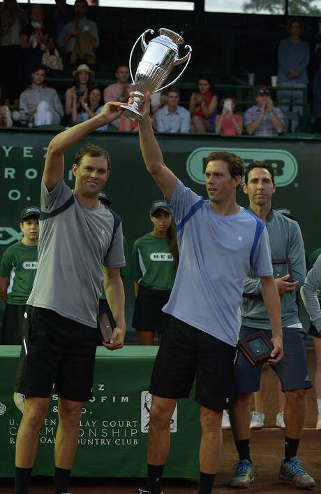 In a familiar rite of spring in Houston, Bob Bryan, left, and his twin brother Mike hoist their U.S. Men's Clay Court Championship trophy after defeating Victor Estrella Burgos and Santiago Gonzalez in the doubles final. Photo: Jerry Baker, Freelance