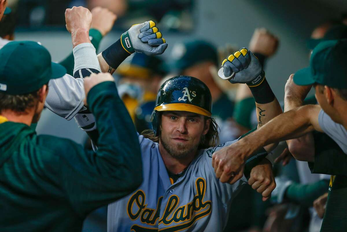 SEATTLE, WA - APRIL 09: Josh Reddick #22 of the Oakland Athletics is congratulated by teammates after hitting a two-run home run in the fifth inning against the Seattle Mariners at Safeco Field on April 9, 2016 in Seattle, Washington. (Photo by Otto Greule Jr/Getty Images)