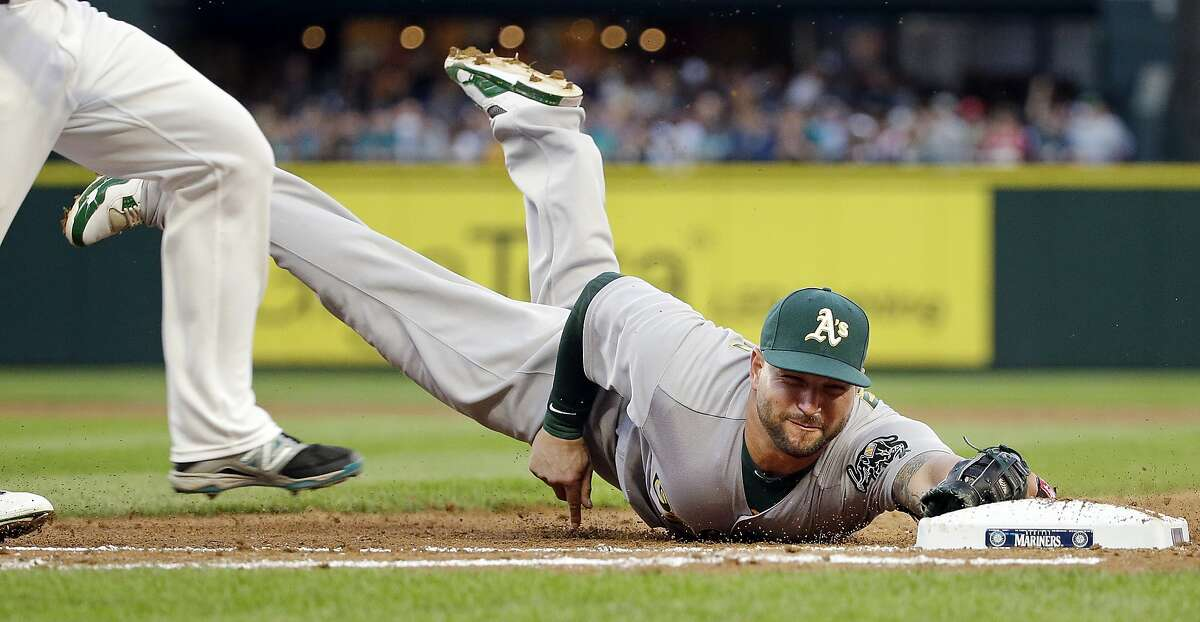 Oakland Athletics first baseman Yonder Alonso dives as he tries to tag first base before Seattle Mariners' Norichika Aoki in the third inning in a baseball game Saturday, April 9, 2016, in Seattle. Aoki was out on the grounder. (AP Photo/Elaine Thompson)