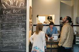 Jenna O'Connell, center, takes an order from customers at the Fowl Boyz pop up in Santa Cruz, Calif. on Saturday, April 2, 2016. The Fowl Boyz pop-up restaurant serves fried quail over waffles and greens.