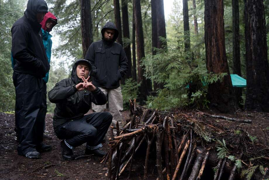 Jack Harrison teaches students how to build a debris hut: Take a large stick, support it with forked sticks and cover it with dead leaves and pine needles. Photo: James Tensuan, Special To The Chronicle