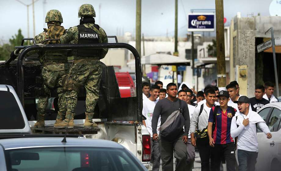 A patrol of Mexican Marines pass by a group of young men in this file photo of Reynosa, Wednesday, April 6, 2016. Security in the city that has no police department has become a major political issue. Photo: Photos By Bob Owen /San Antonio Express-News / San Antonio Express-News