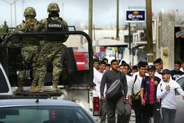 A patrol of Mexican Marines pass by a group of young men on their way to a rally for Tamaulipas gebernatorial PAN candidate Baltazar Hinojosa Ochoa in Reynosa, Wednesday, April 6, 2016. Security in the city that has no police department has become a major political issue.