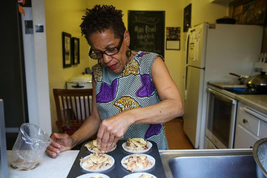 Renée McGhee sprinkles brown sugar on bread pudding as she bakes in her kitchen in Berkeley. She works with Josephine. Photo: Gabrielle Lurie, Special To The Chronicle