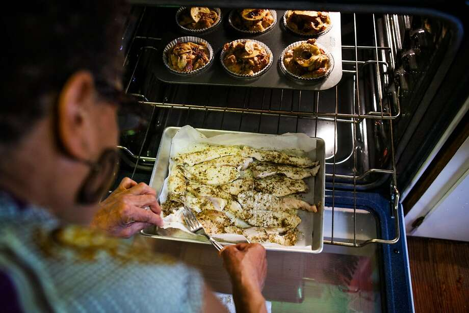 Renee McGhee checks on the chicken cooking in her oven in Berkeley, California, on Thursday, April 7, 2016. Renee works for a website called Josephine, where she makes meals in her kitchen and customers come to her home to pick up food after purchasing through the site. Photo: Gabrielle Lurie, Special To The Chronicle