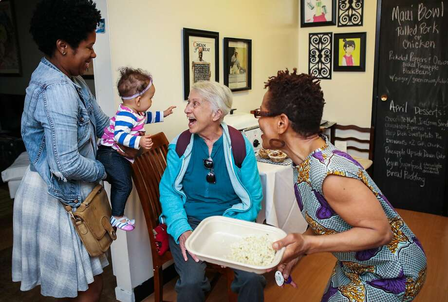 Customer Lois Sharpnack (center) greets Olivia Lee Rose (second from left), 8 months, the granddaughter of Renne McGhee (right), as Renee packages a meal for Lois in her kitchen in Berkeley, California, on Thursday, April 7, 2016. Renee works as a cook for the website Josephine, that aims to connect home cooks with local customers. Customers pick up food directly from the cooks homes after purchasing through the site. (Also pictured is Renee's daughter, Shauntee Edwards at left.) Photo: Gabrielle Lurie, Special To The Chronicle