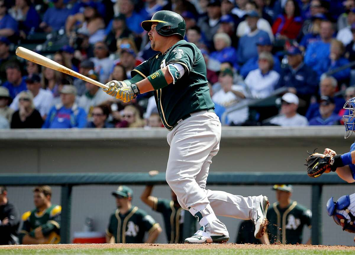 Oakland Athletics Billy Butler follows through on an RBI double against the Chicago Cubs during the first inning of a spring training baseball game, Tuesday, March 29, 2016, in Mesa, Ariz. (AP Photo/Matt York)