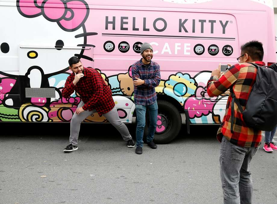 Two men pose for a photograph in front of a Hello Kitty Cafe van parked during the annual Cherry Blossom festival in Japantown in San Francisco, California in 2016. Photo: Connor Radnovich / The Chronicle