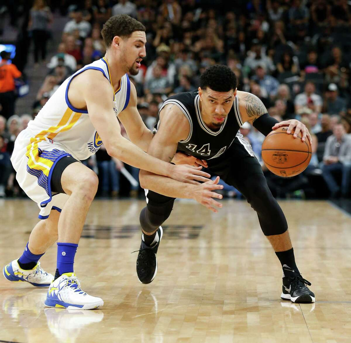 Spurs' Danny Green (14) attempt to drive around Golden State Warriors' Klay Thompson (11) at the AT&T Center on Sunday, Apr. 10, 2016.