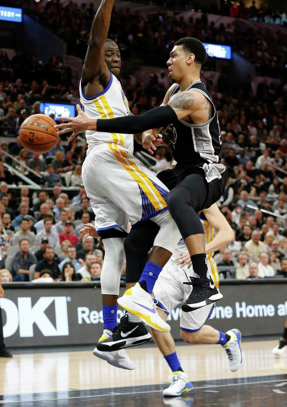 Spurs' Danny Green (14) pass the ball around Golden State Warriors' Draymond Green (23) at the AT&T Center on Sunday, Apr. 10, 2016.