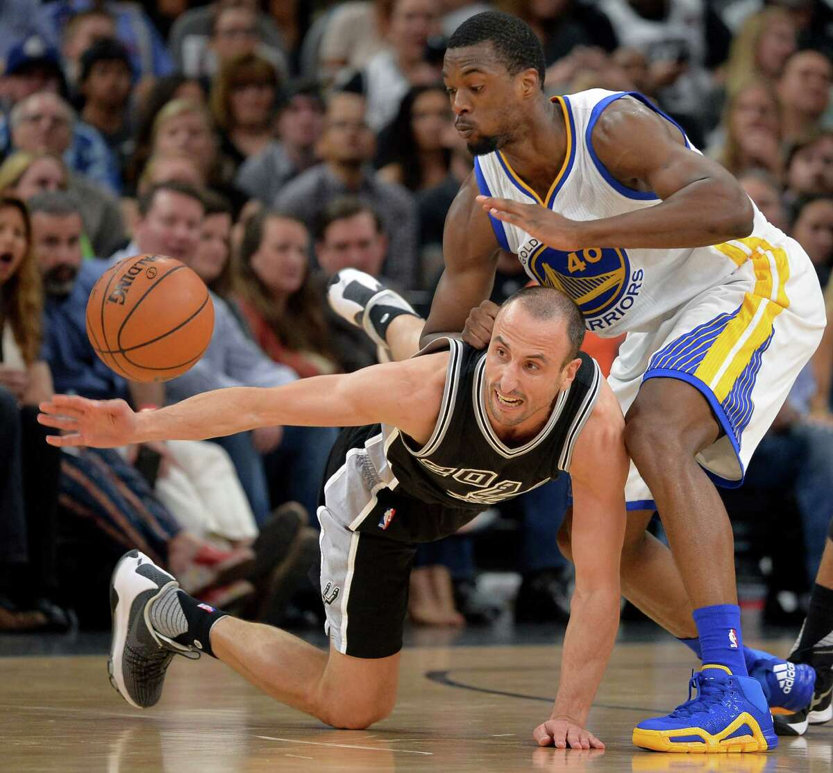 San Antonio Spurs' Manu Ginobili, bottom, of Argentina, chases the ball against Golden State Warriors' Harrison Barnes during the first half of an NBA basketball game, Sunday, April 10, 2016, in San Antonio. (AP Photo/Darren Abate)