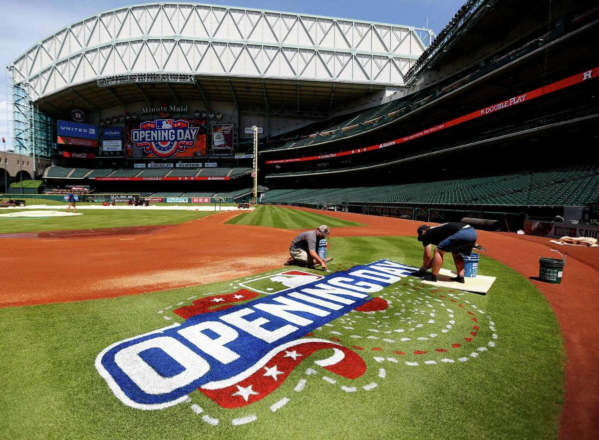 Minute Maid Park grounds crew members prepare for the Houston Astros home opener on Monday.