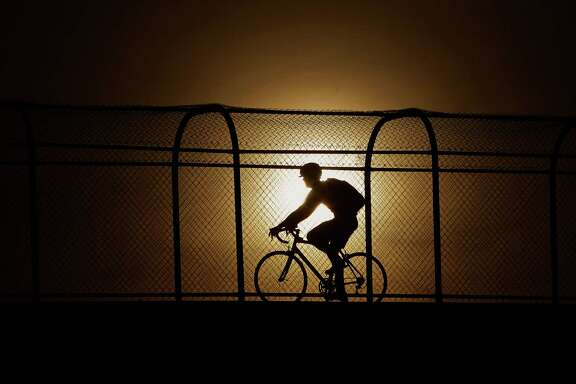 Cool temperatures and a beautiful sunrise made a great morning for early workouts, like this cyclists crossing the Jackson Hill bridge over Memorial, Thursday, April 7, 2016, in Houston.